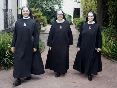 Fotografía de tres religiosas de la Cruz del Sagrado Corazón revestidas con el hábito de su orden.
