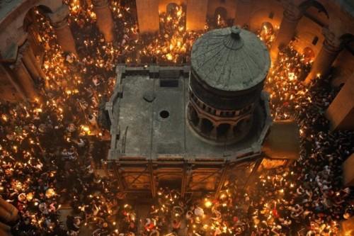 Vista de la edícula en el interior de la Basílica, rodeada por fieles con velas con ocasión de la Noche de Pascua. Basílica del Santo Sepulcro, Jerusalén (Israel).