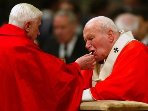 El cardenal Joseph Ratzinger -futuro papa Benedicto XVI- da la comunión en la boca al papa San Juan Pablo II.