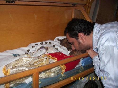 Un fiel besa las reliquias de un bebé, colocado junto a su madre. Monasterio de los Mártires, Akhmim (Egipto).