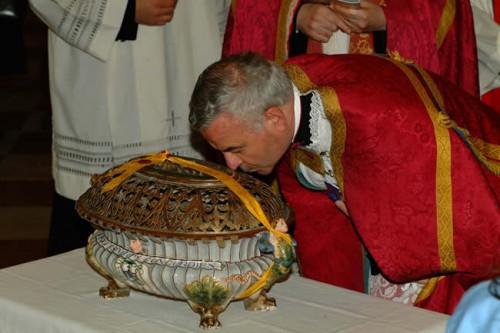 Un sacerdote besa el relicario con los restos de los mártires de Aquileya. Concordia Sagittaria, Italia.