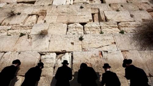 Fotografía del Muro de las Lamentaciones en Jerusalén (Israel), con rabinos ortodoxos rezando.