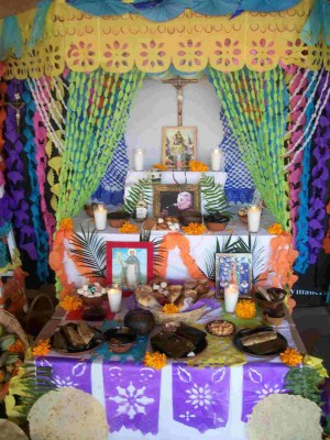 Altar mestizo adornado con papeles de colores.