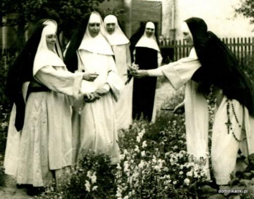 Fotografía de la Beata recogiendo flores en el jardín del convento y entregándolas a sus compañeras.