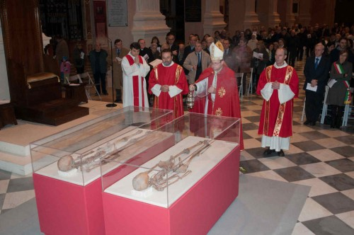 Veneración de los restos de los santos en sus dos urnas. Catedral de Reggio Emilia, Italia.