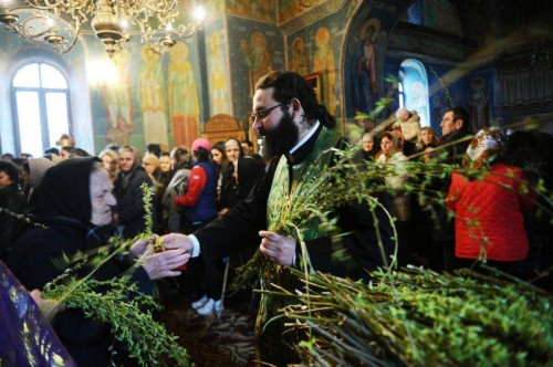 Domingo de Ramos: el sacerdote rumano reparte ramas de sauce entre los cristianos de la iglesia.