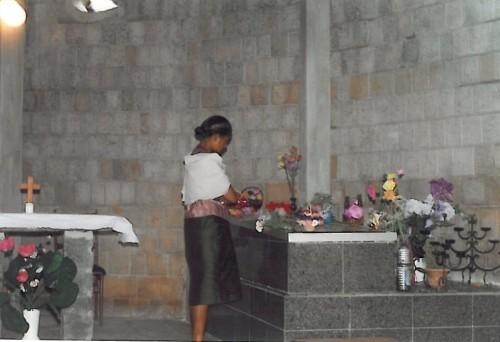 Una devota malgache depositando una ofrenda floral sobre la tumba de la Beata.