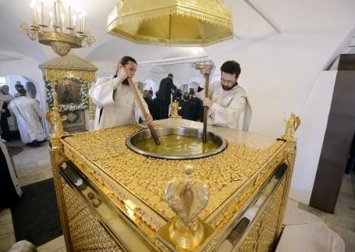 Dos diáconos preparan el santo crisma antes de ser consagrado en la Misa Crismal.