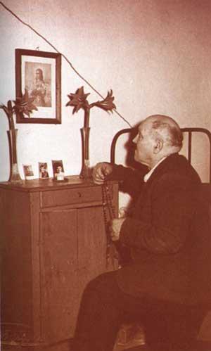 Alessandro Serenelli, ya anciano, reza el rosario ante un cuadro de Santa María Goretti.