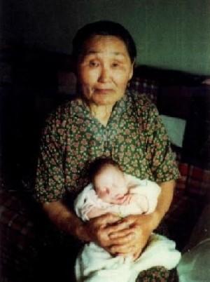 Fotografía de Santa Olga Michael con uno de los bebés que ayudaba a traer al mundo.