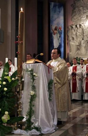 Diácono cantando en Pregón Pascual ante el Cirio Pascual.