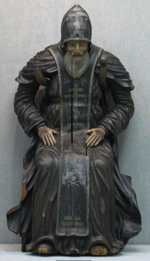 Escultura del santo sentado y en oración.