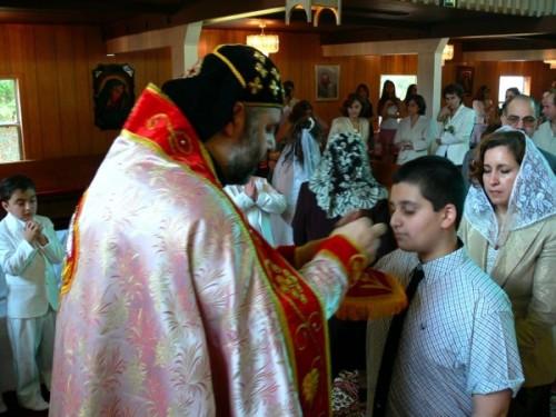 Sacerdote ortodoxo sirio administrando la comunión en una misa.
