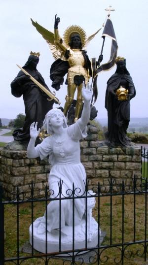 Aparición de San Miguel Arcángel y las Santas Catalina de Alejandría y Margarita de Antioquía a Juana de Arco. Conjunto escultórico conmemorativo en Domrémy-la-Pucelle (Francia).