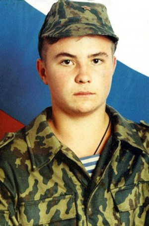 Fotografía de Eugenio Rodionov vestido de soldado, al fondo la bandera rusa.