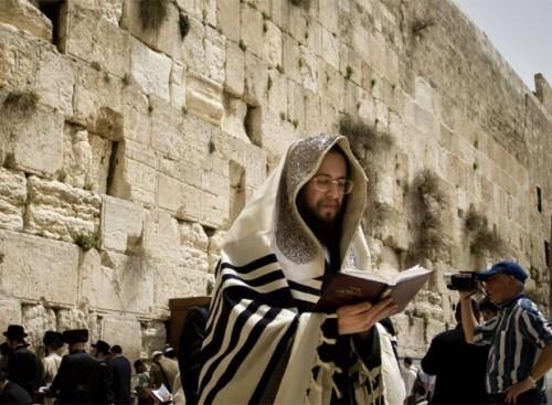 Fotografía de un rabino, orando con el Muro de las Lamentaciones a su espalda. Jerusalén (Israel).