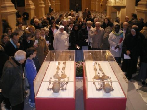 Un grupo de visitantes contempla los esqueletos recuperados y reconstruidos de los Santos. Catedral de Reggio Emilia, Italia.