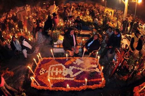 Personas reunidas en la noche de difuntos en el panteón de Mixquic.