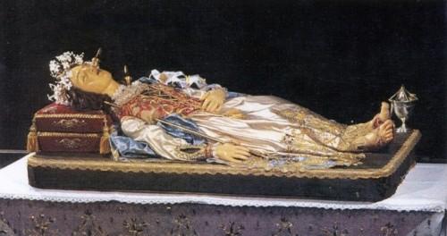 Imagen yacente de la Beata que contiene sus reliquias (los husos clavados en la cabeza, cuello y pecho indican las heridas mortales). Ghemme, Italia.