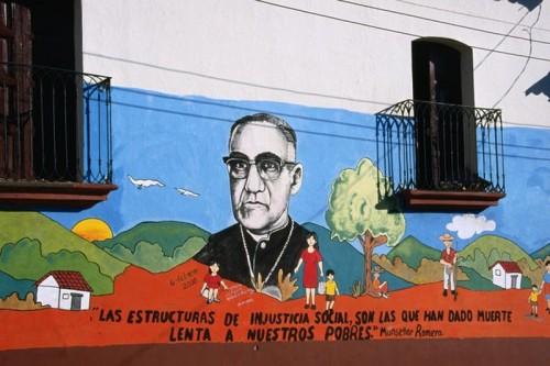 """Mural del Siervo de Dios en una calle de El Salvador con una cita suya: """"Las estructuras de injusticia social son las que han dado muerte lenta a nuestros pobres""""."""