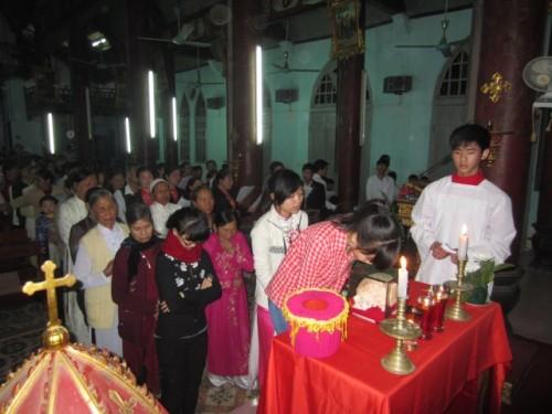 Fieles vietnamitas besando el relicario del cráneo.