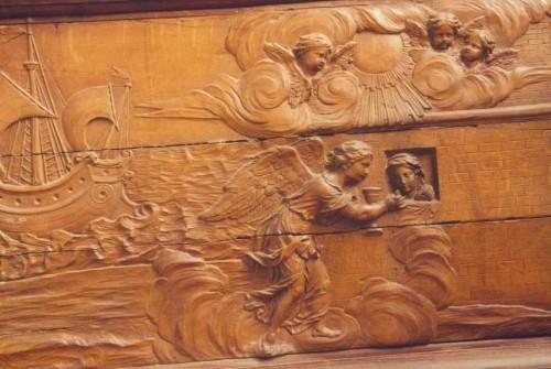 Santa Avia recibe de la comunión en prisión, de manos de un ángel. A la derecha, una de las naves de la compañía de Santa Úrsula. Relieve en madera. Colegiata de Nuestra Señora de Vernon, Canadá.