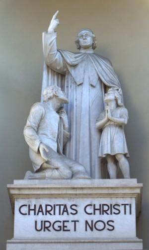 """Grupo escultórico del Santo con su lema: """"El amor de Cristo nos urge""""."""